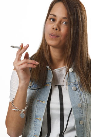 twenty something girl in trendy outfit, smoking a cigarette 免版税图像 - 56345665