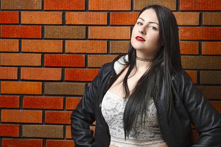 twenty something: twenty something girl standing against a brick wall Stock Photo