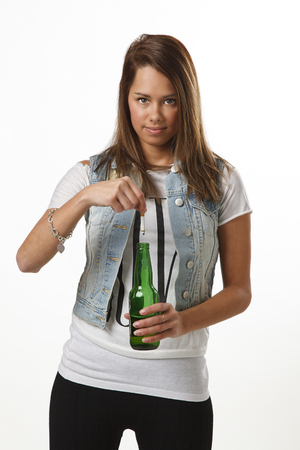 twenty something: twenty something girl putting out her cigarette into a green bottle beer Stock Photo