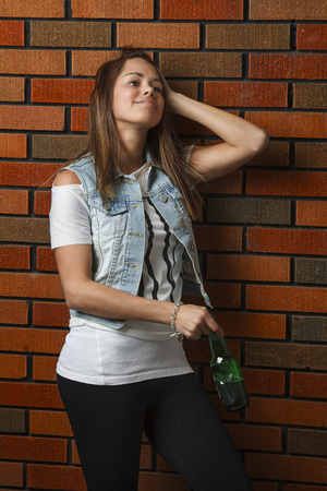 twenties: early twenties woman against a bick wall, holding green bottle of beer Stock Photo