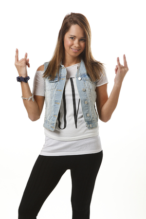 twenty something: twenty something girl in trendy outfit doing the rock and roll sign
