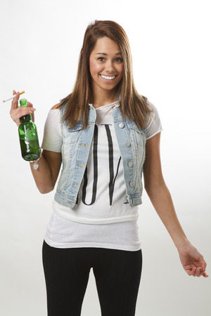 twenty something: twenty something girl in trendy outfit, drinking a beer and having a cigarette