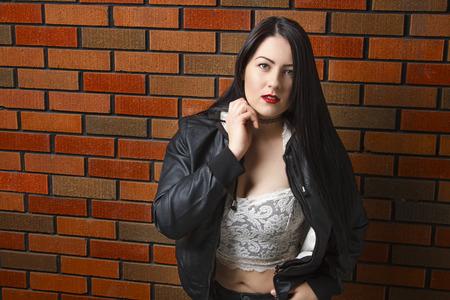 twenty something: sexy twenty something girl with lace top against brick wall