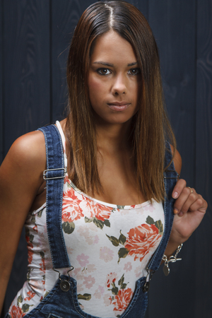 twenty something: twenty something girl beautiful with floweral pattern tank top and jeans overalls