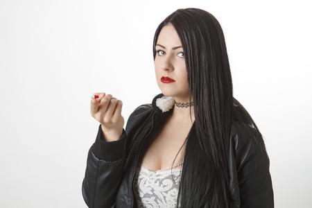 twenty something: twenty something girl holding a red and white pill on the tip of her finger