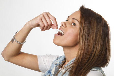 twenty something girl putting a pill in her mouth Stock Photo