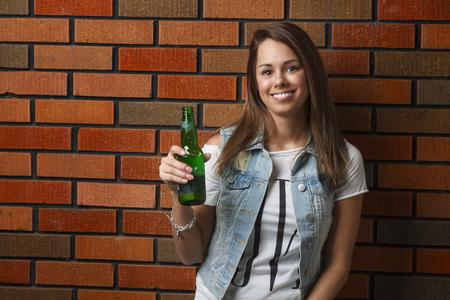 twenty something: twenty something girl holding a green bottle of beer against a brick wall