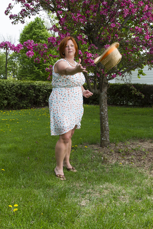 forty something woman wearing a summer dress, throwing a straw hat