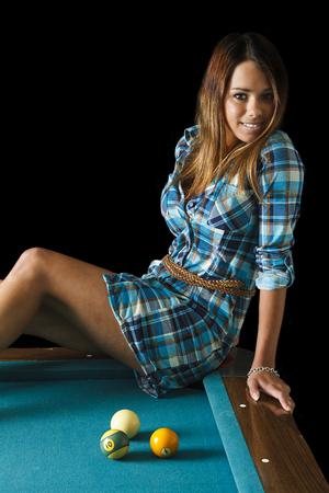 twenty something beautiful girl wearing a low cut plaid shirt sitting on the corner of a pool table Archivio Fotografico