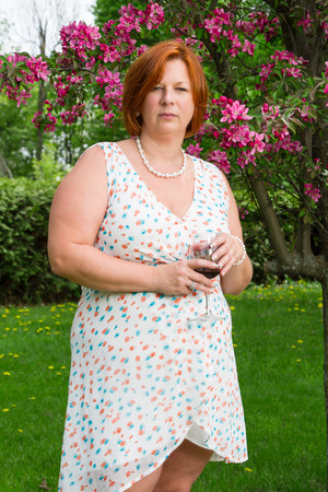 forty year old woman in summer dress, having a glass of wine under a cherry tree