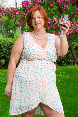 woman in her forties, wearing a summer dress, cheering with a glass of red wine