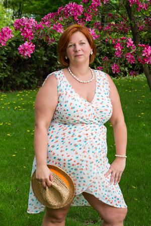 Donna di mezza età in piedi sotto un albero di ciliegio, in possesso di un cappello di paglia Archivio Fotografico - 85632391