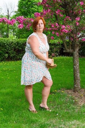 forty something brunette woman wearing a sun dress throwing a hat Standard-Bild