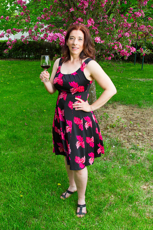 forty something brunette woman wearing a sun dress enjoying a glass of wine
