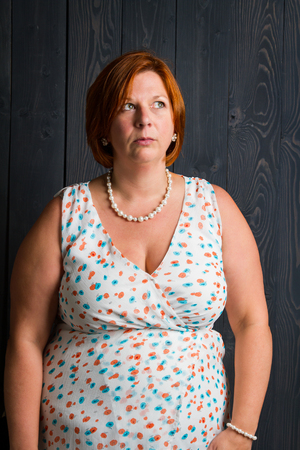 forty year old woman wearing a summer dress, in front of a blue stain wood panel background, with perplexe look Reklamní fotografie