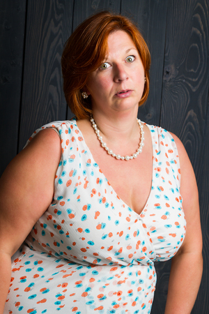 forty year old woman wearing a summer dress, in front of a blue stain wood panel background, with a annoyed expression Stock Photo