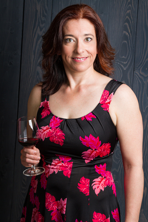 forty something brunette woman wearing a sun dress in front of blue wood panel with a glass of red wine Imagens