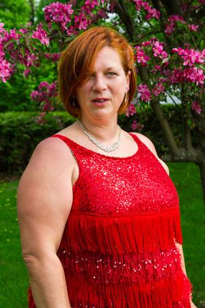 vrouw van in de veertig, gekleed in een sprankelende jurk, onder een kersenboom