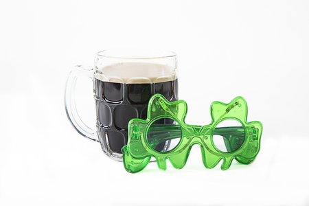 black beer in a cheap glass and green shamrock glasses
