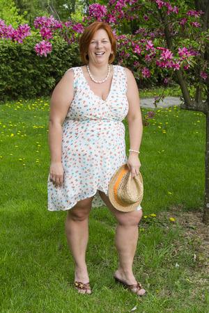 Quaranta qualcosa di donna sotto un ciliegio in possesso di un cappello di paglia Archivio Fotografico - 90951041