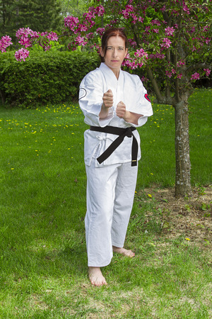 forty something martial artist woman in fighting stance, under a cherry tree