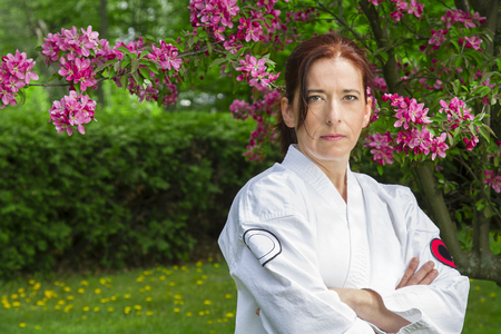 forty something martial artist woman with serious glare, under a cherry tree
