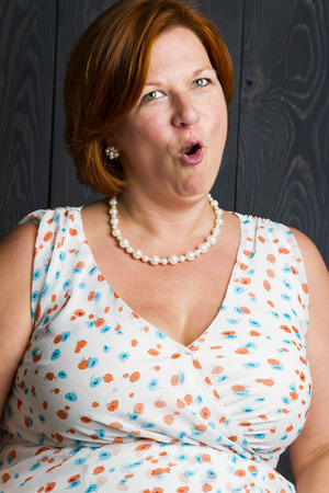 forty something woman wearing a sundress in front of a blue stain background, doing a surprise