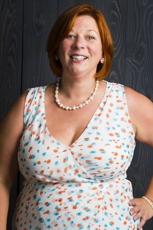 woman in her forties, in front of a blue stain wood background, with a great smile