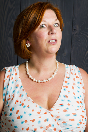 forty something red haired woman, wearing a sundress in front of a blue stain background, with angry look