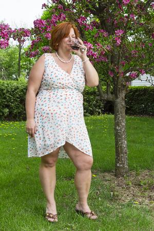 roodharige vrouw, in de veertig, die een slokje rode wijn neemt onder een bloeiende kersenboom