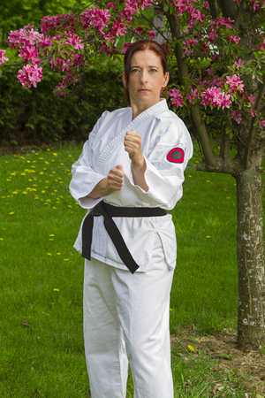 forty something brunette woman, wearing a wearing karate gi, standing under a cherry tree, doing a punch stance
