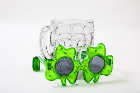 small pair of st-patties days sunglasses and an empty beer mug Imagens