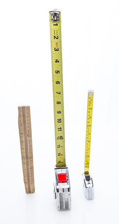 wood rulers and two different mesuring tape place vertically
