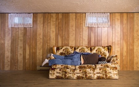 man sleeping on his side, on an old basement couch