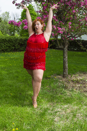 woman in her forties, wearing a sparkly dress, under a tree, doing a lady styling pose, doing a funny face Standard-Bild