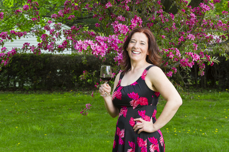 forty something brunette woman, wearing a summer dress, in front of a cherry tree, having a glass of red wine