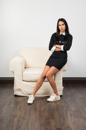 woman sittin on the arm of a couch with her arms cross Zdjęcie Seryjne