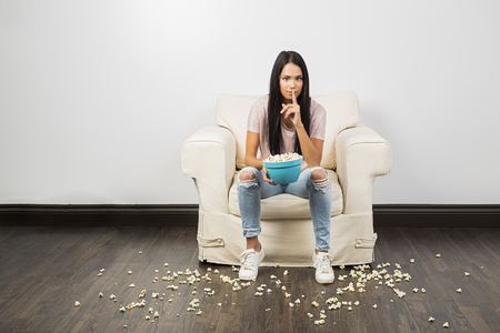 Young woman holding a bowl of popcorn and doing the silence sign