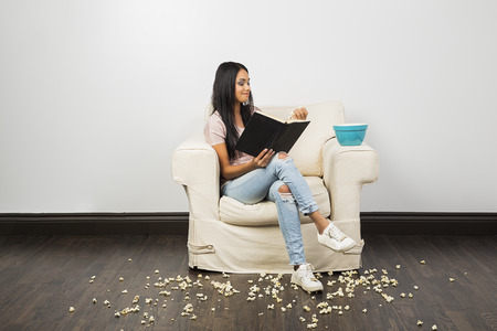 young woman sitting on couch, reading a book and eating popcorn while leaving a mess Reklamní fotografie