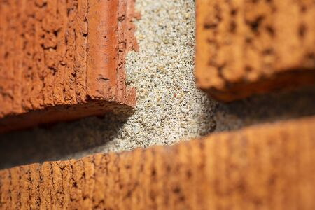 Macro shot of a jonction of red brick on a wall
