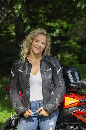 Cute blonde woman wearing a black leather jacket, standing in front of a motocycle