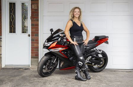 Happy twenty something woman, leaning on a sport motocycle, in front of garage door