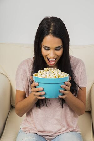 Young woman with mouth wide open over a blue bolw filled with popcorn Stock fotó