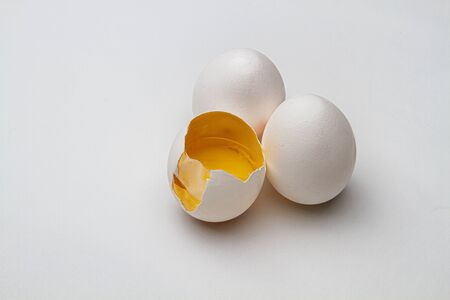 two ful egg, on egg with it's top crack open, exposed inside skin and yoke
