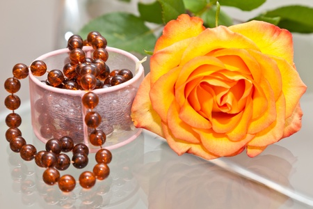 Yellow rose on a table and an amber beads Stock Photo - 10638315