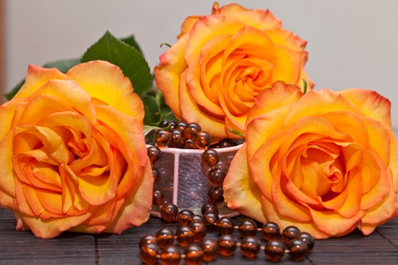 Yellow rose on a table and an amber beads photo