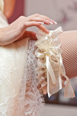 stockings feet: Garter on a foot of the bride