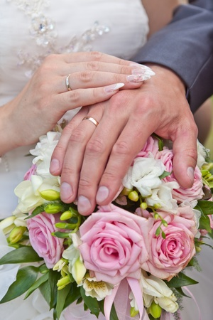 Hands of the groom and the bride with rings on a wedding bouquet photo