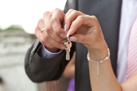 Hands holding keys from doors Stock Photo