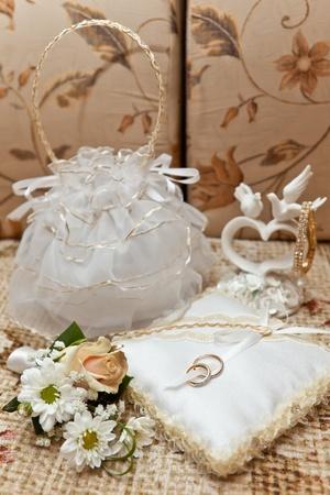 Wedding rings on a small pillow, a handbag, a buttonhole